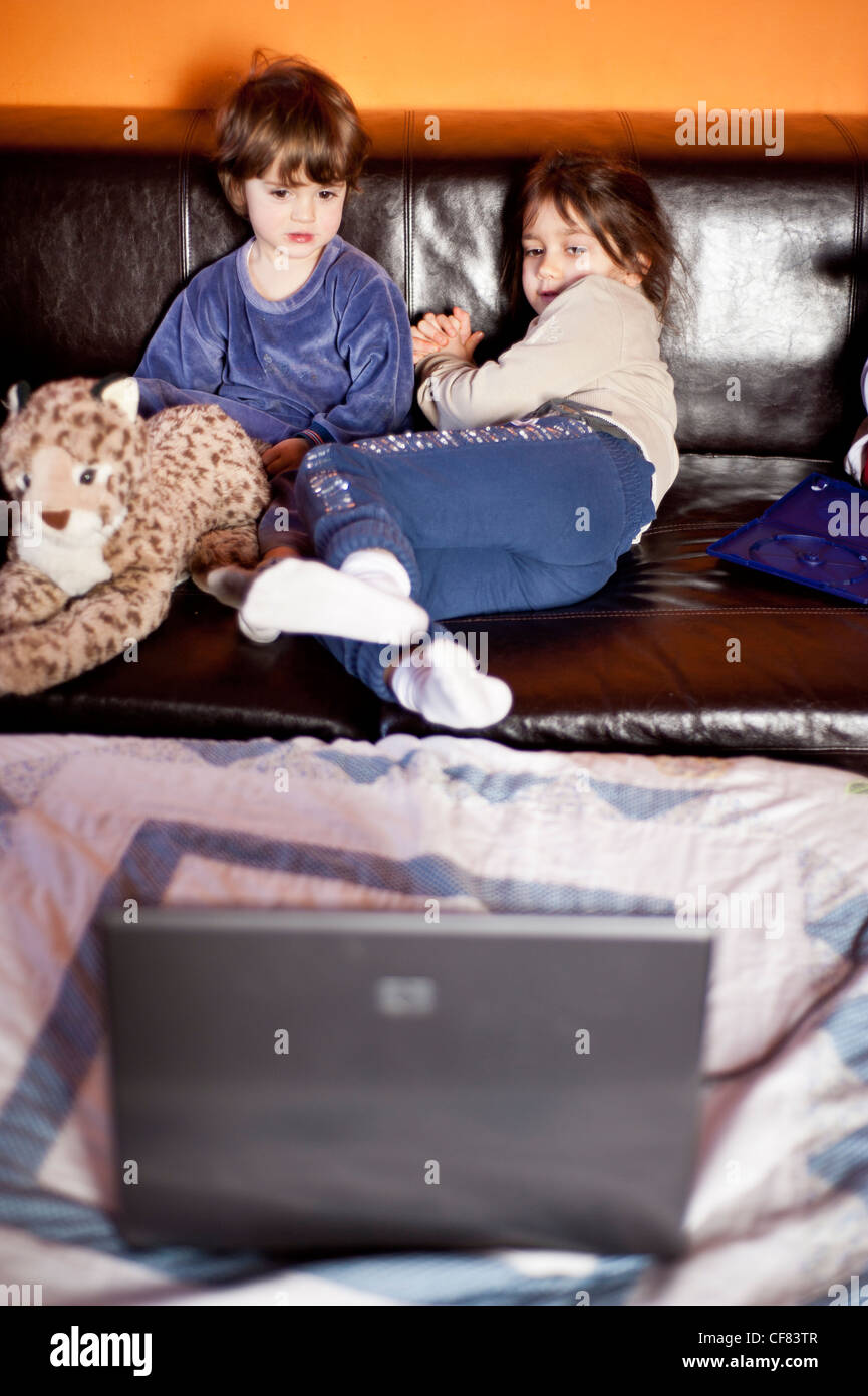 children watch computer in a messy house - Stock Image