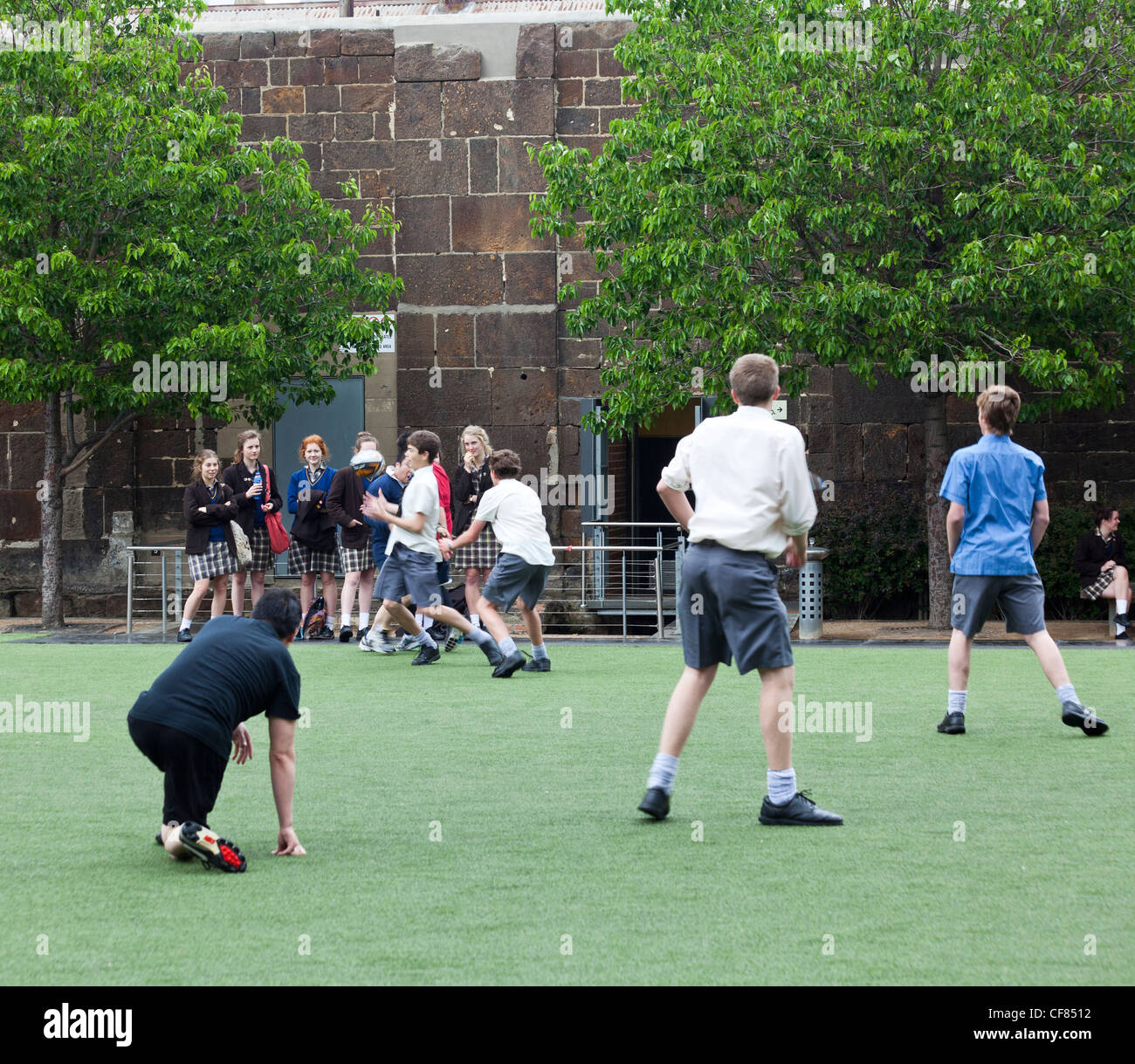 schoolboys playing touch rugby watched by admiring schoolgirls, Melbourne, Australia - Stock Image