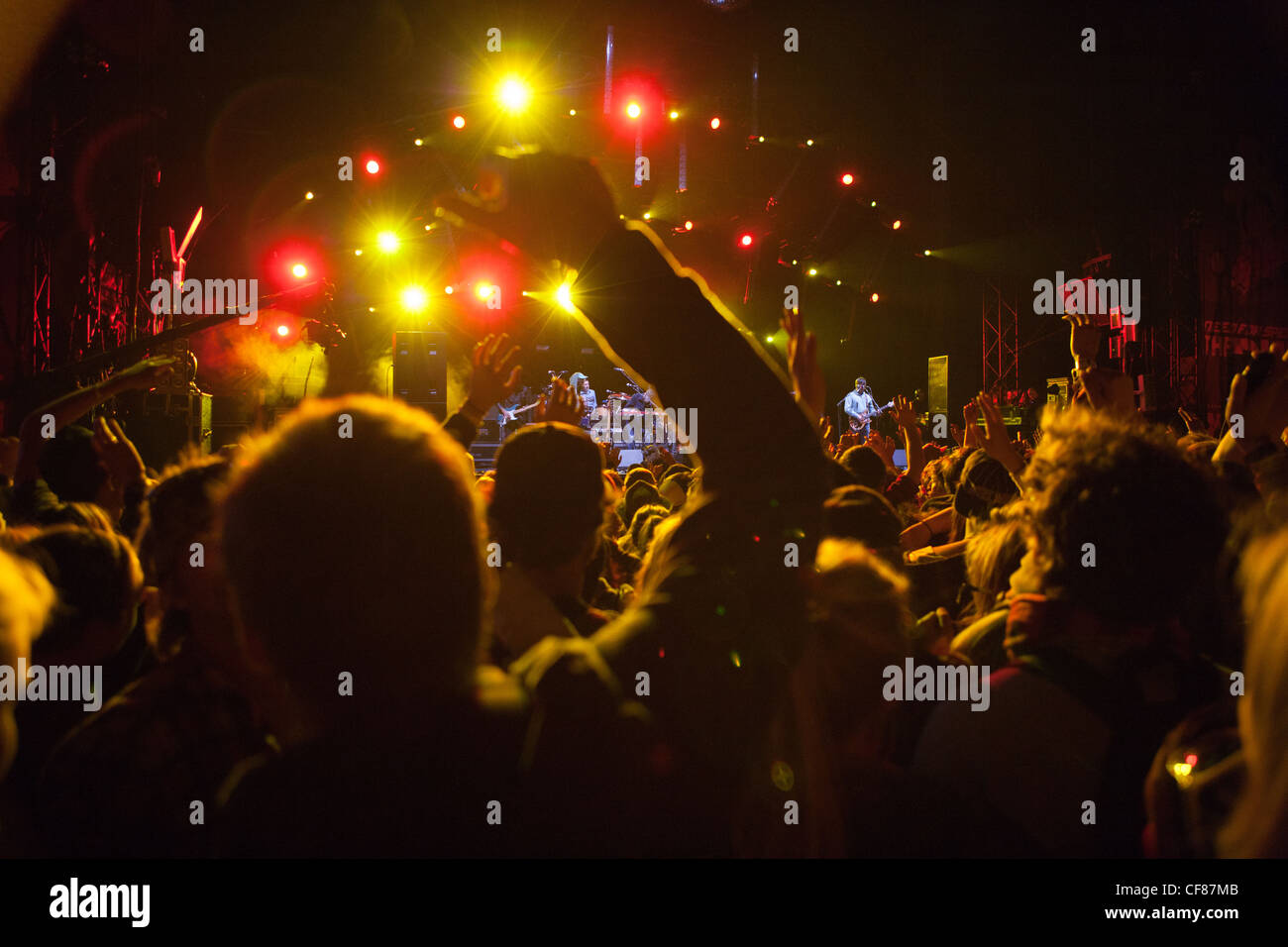 Crowd cheering at an outdoor concert at night. - Stock Image