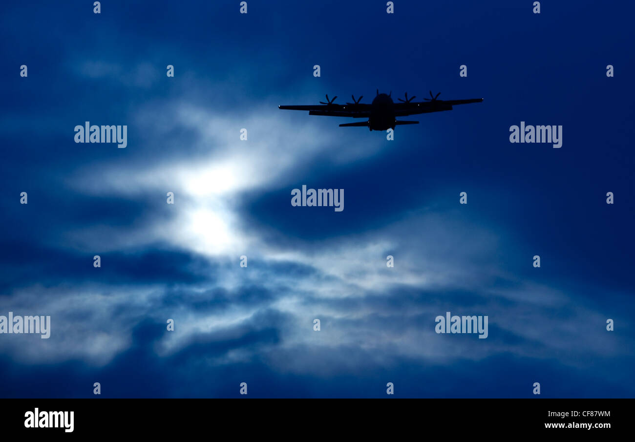 A Hercules military transport plane silhouetted against a dark blue sky. - Stock Image