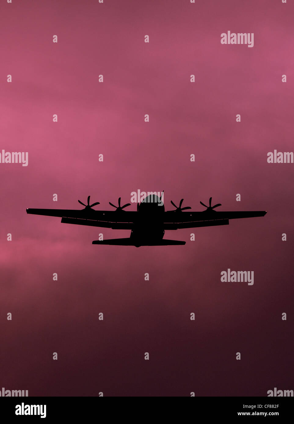 A Hercules military transport plane silhouetted against a magenta / red sky - Stock Image