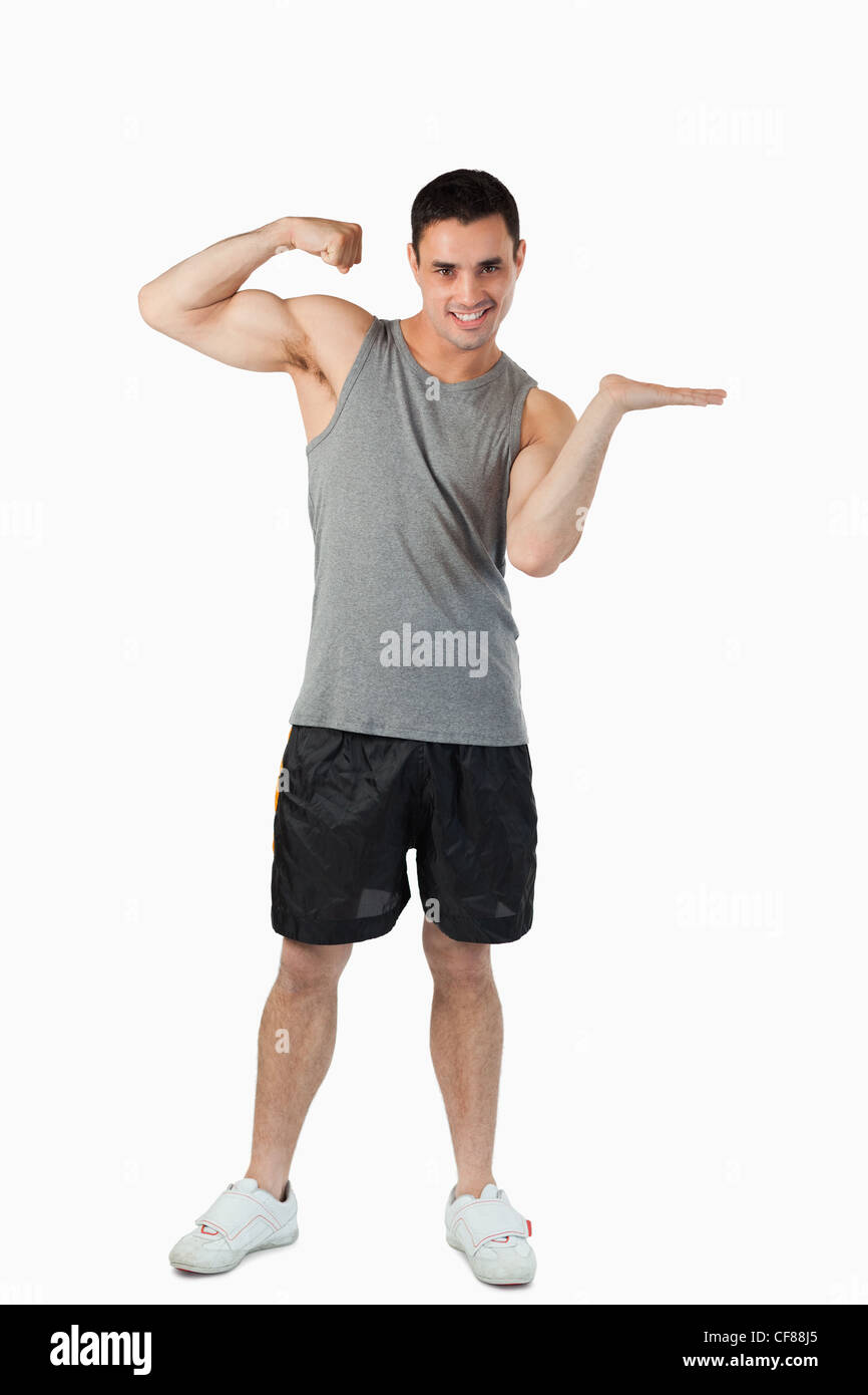 Young man showing his biceps while presenting - Stock Image