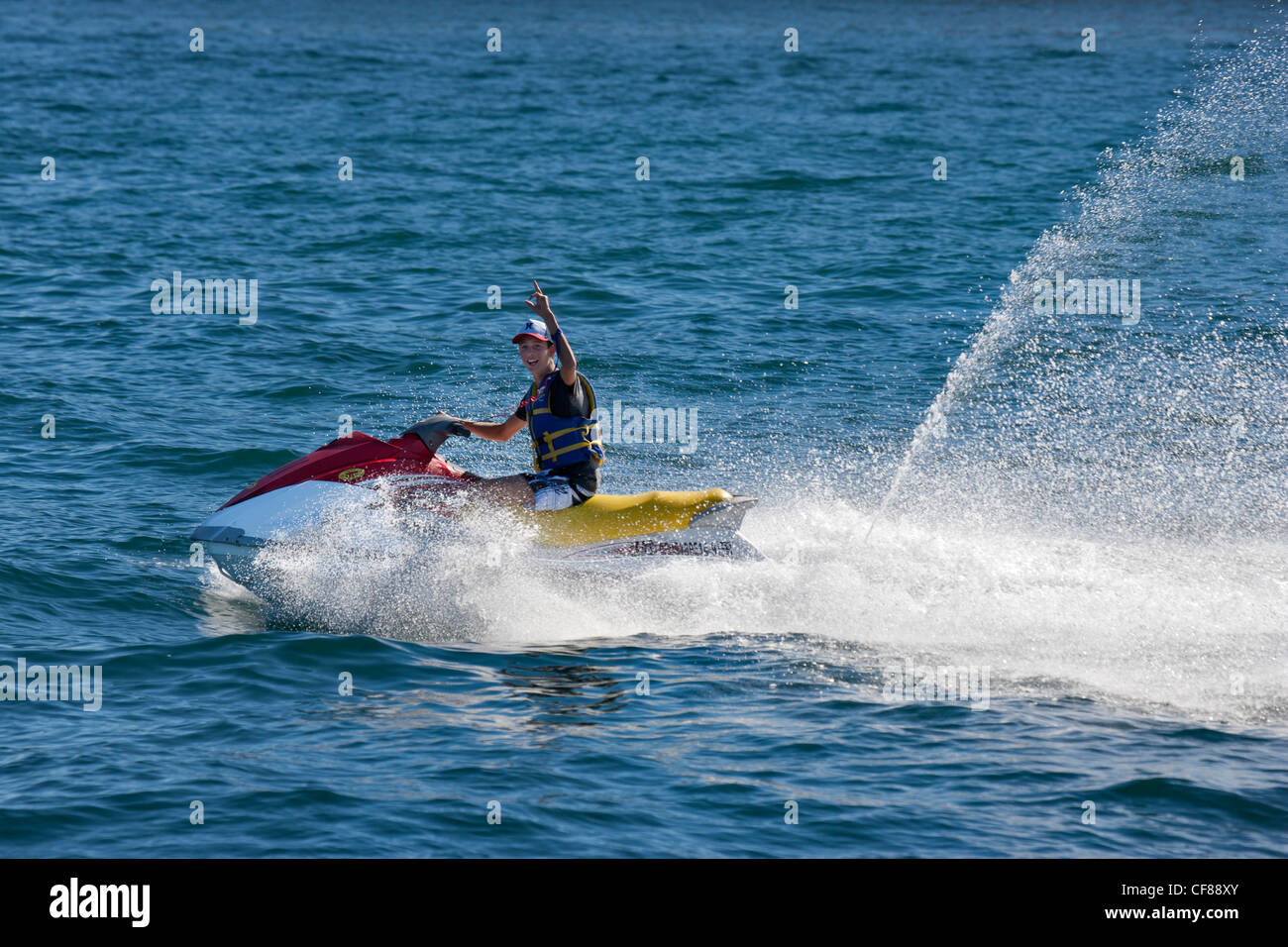 Young man speeding over the Sea of Cortez in the Pacific Ocean in a jetski watercraft near Cabo San Lucas-Mexico. - Stock Image