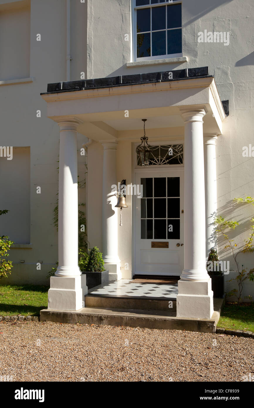 Portico and front door of white stucco country house with large hanging doorbell & Portico and front door of white stucco country house with large ...