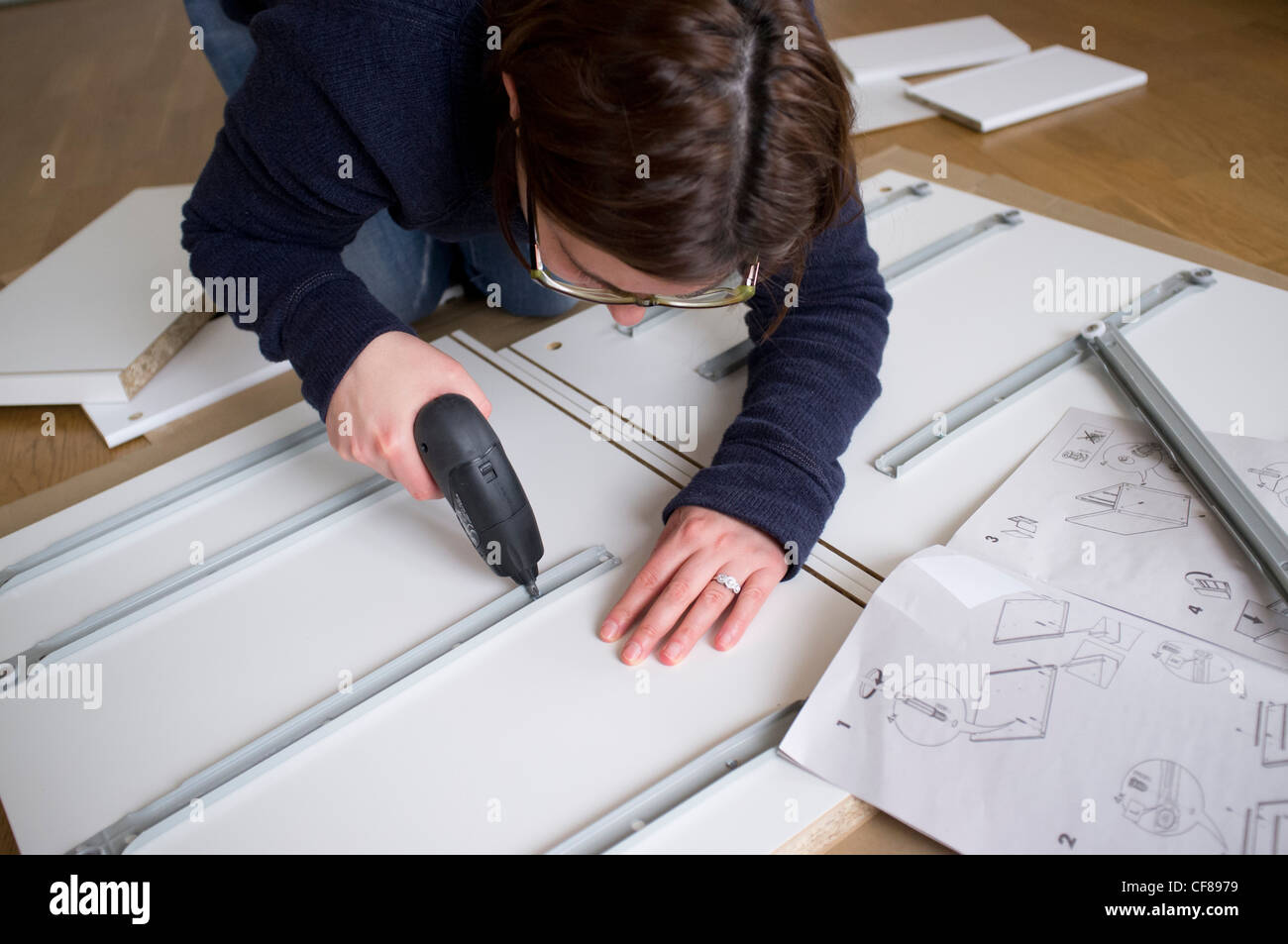 Woman assembling flat-pack furniture from IKEA at home - Stock Image
