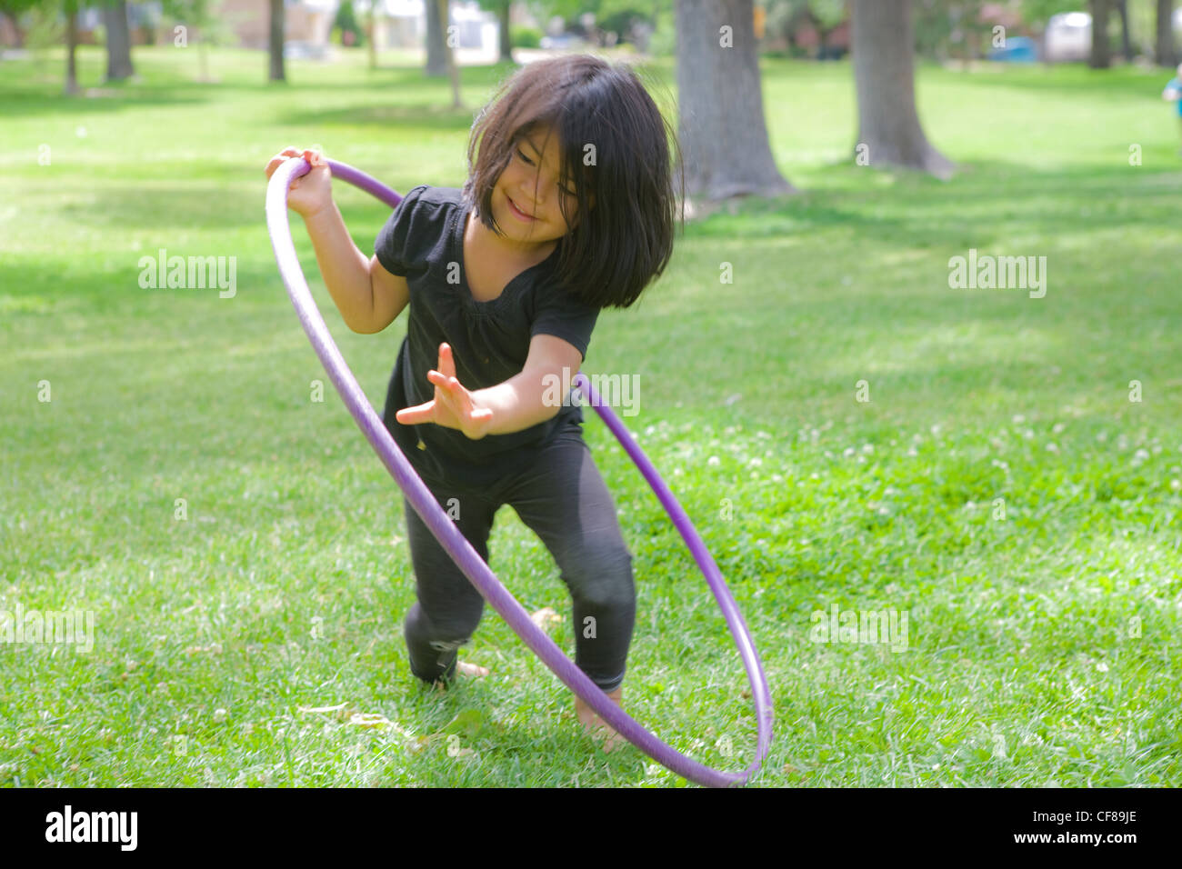 Four year old girl playing with a hoolahoop in a park. - Stock Image