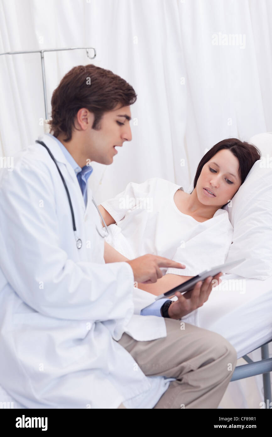 Doctor showing his patient whats on his tablet - Stock Image