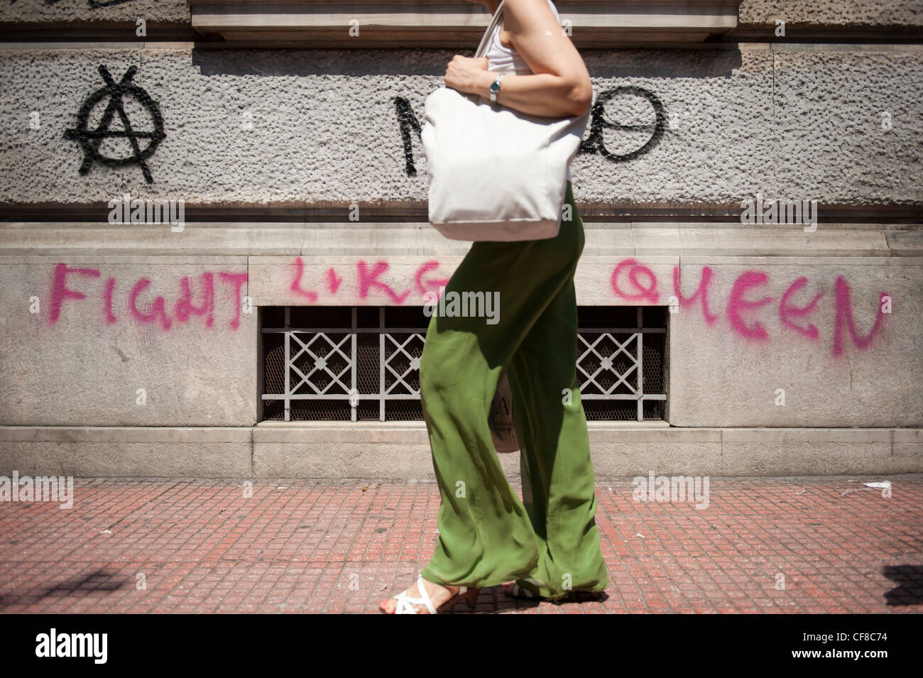A woman walks in Panepistimiou Str, central Athens by a graffiti writing 'Fight like a Queen' - Stock Image