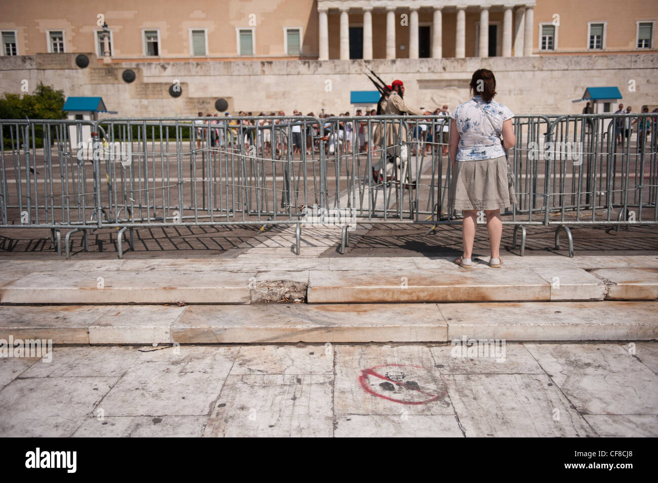 A tourist looking at the fenced tomb of the unknown soldier in Syntagma Sq After the riots of June 2011 the area - Stock Image