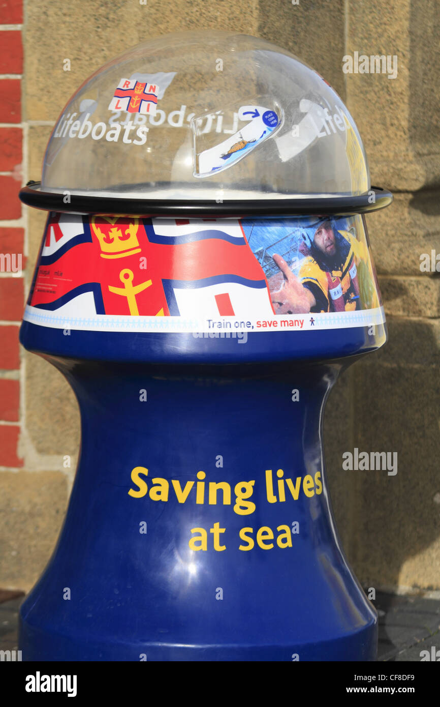 A charity donation collection box for the Royal National Lifeboat Institution RNLI. - Stock Image