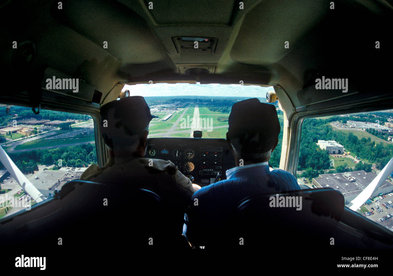 A Cessna plane coming in for a landing in an airport. - Stock Image