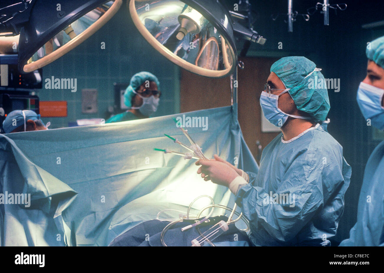 A surgeon performing surgery on a patient in the operating room. - Stock Image