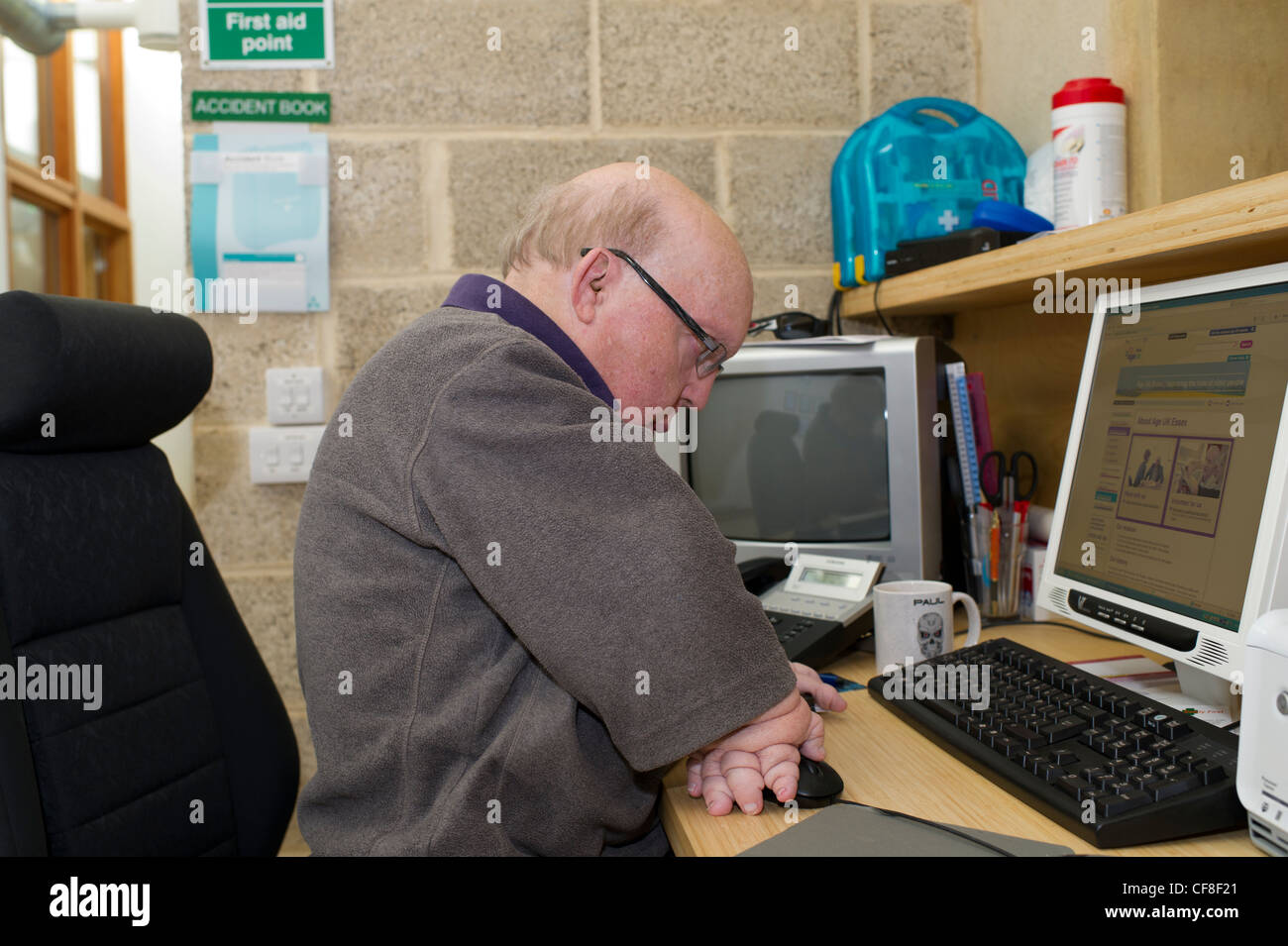 A disabled male with multiple congenital deformities working on the telephone helpline at the headquarters of Disability Stock Photo
