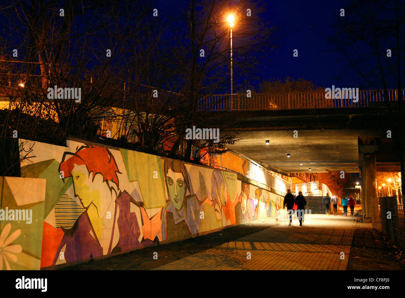 Public walk path, underneath a street bridge, with lots of graffiti, at night. Essen, Germany. - Stock Image
