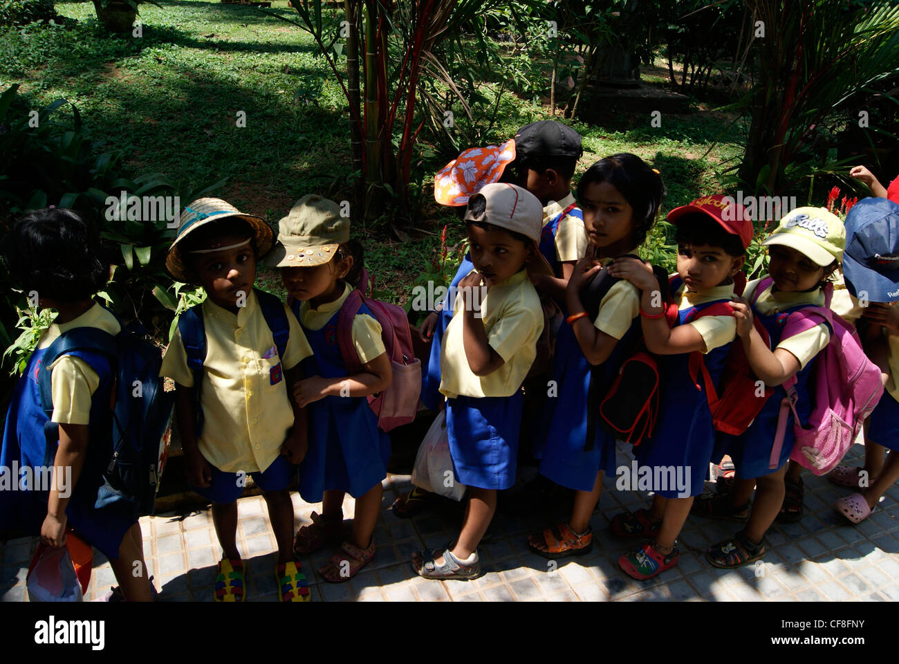 Small Nursery School Children standing in Queue for entering school Bus.A Scene from Kerala,India - Stock Image