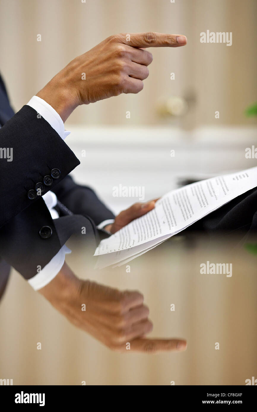 President Barack Obama hand is reflected on his desk as he gestures during a speech prep meeting in the Oval Office - Stock Image