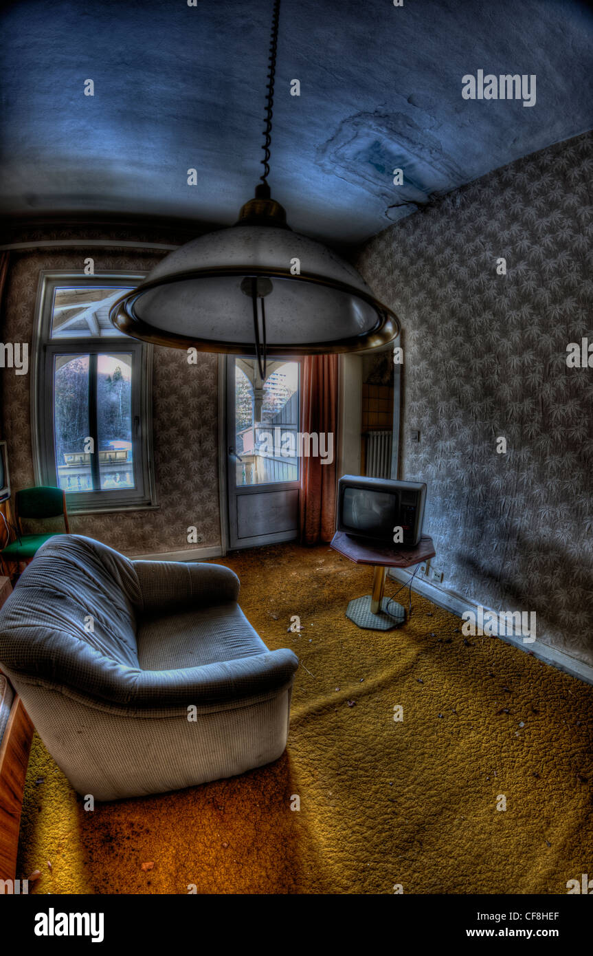 Interior of disused hotel near East German border with grey interior sofa television and ceiling light - Stock Image