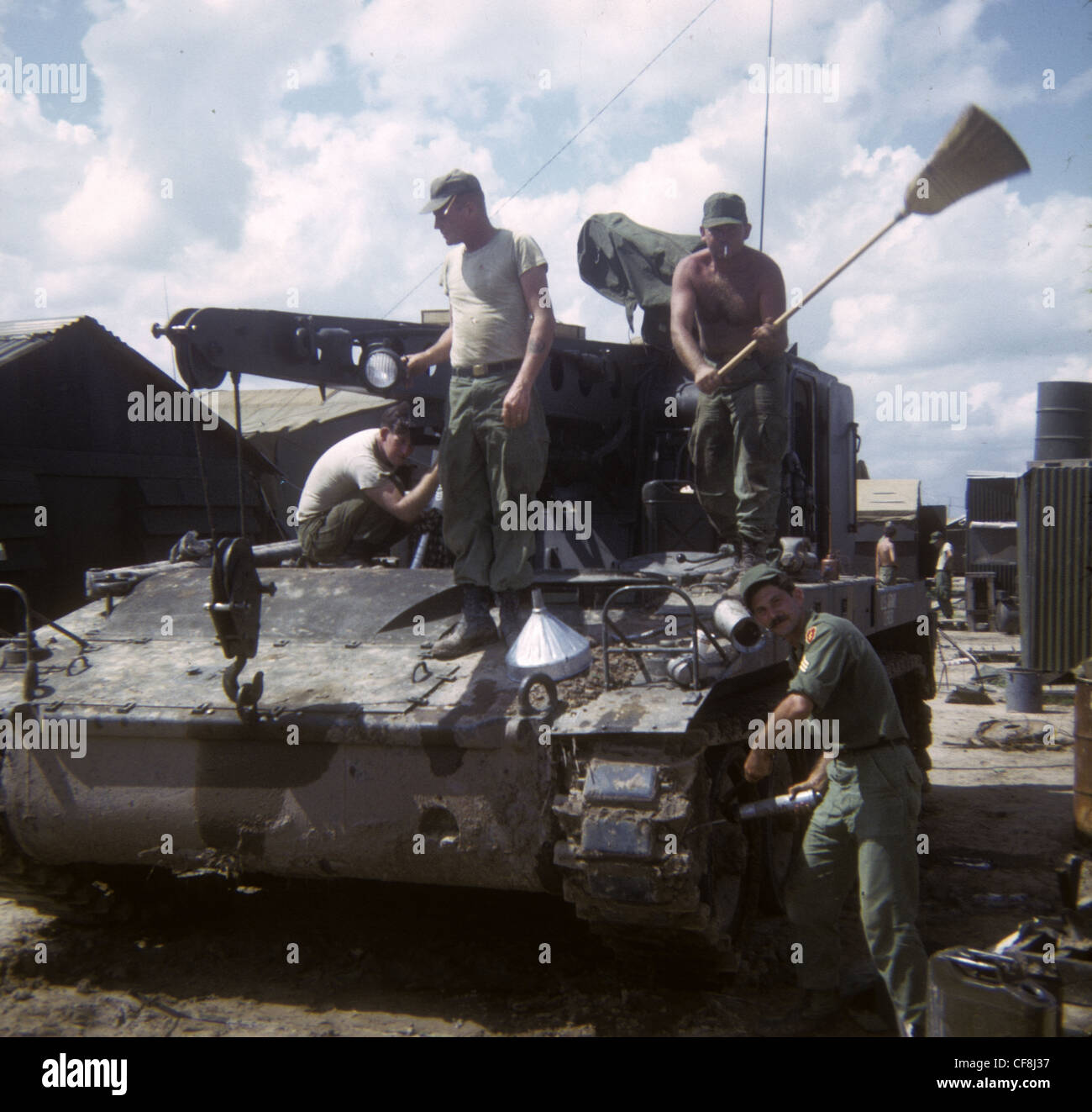 American soliders cleaning dirty muddy APC 1/5th (Mechanized) Infantry CU CHI VIETNAM War 1966 M113 armored personnel - Stock Image