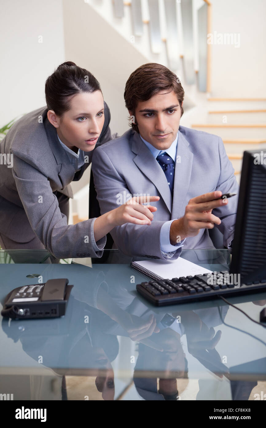 Businessman showing whats on his screen to his colleague - Stock Image