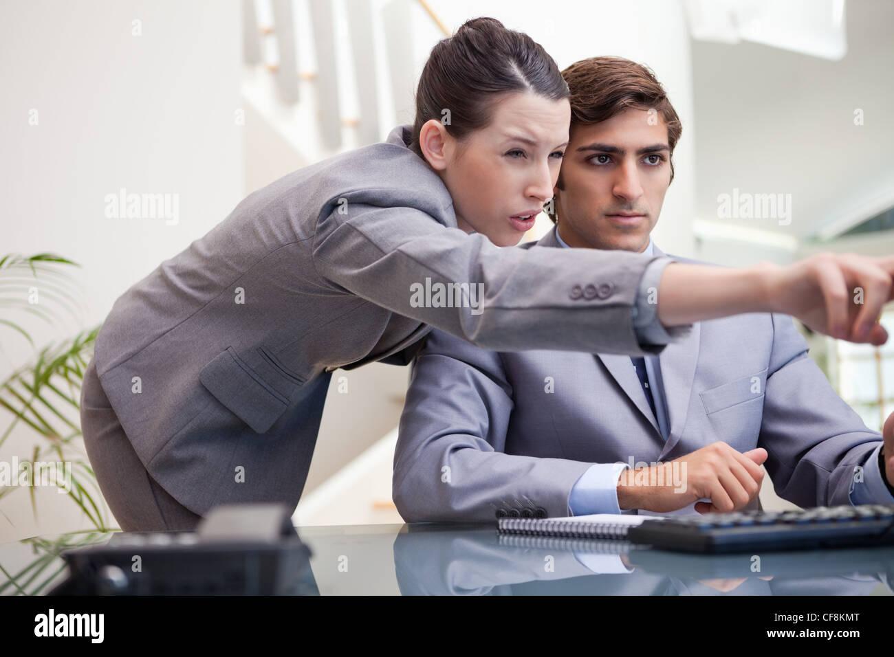 Businesswoman explaining computer program to colleague - Stock Image