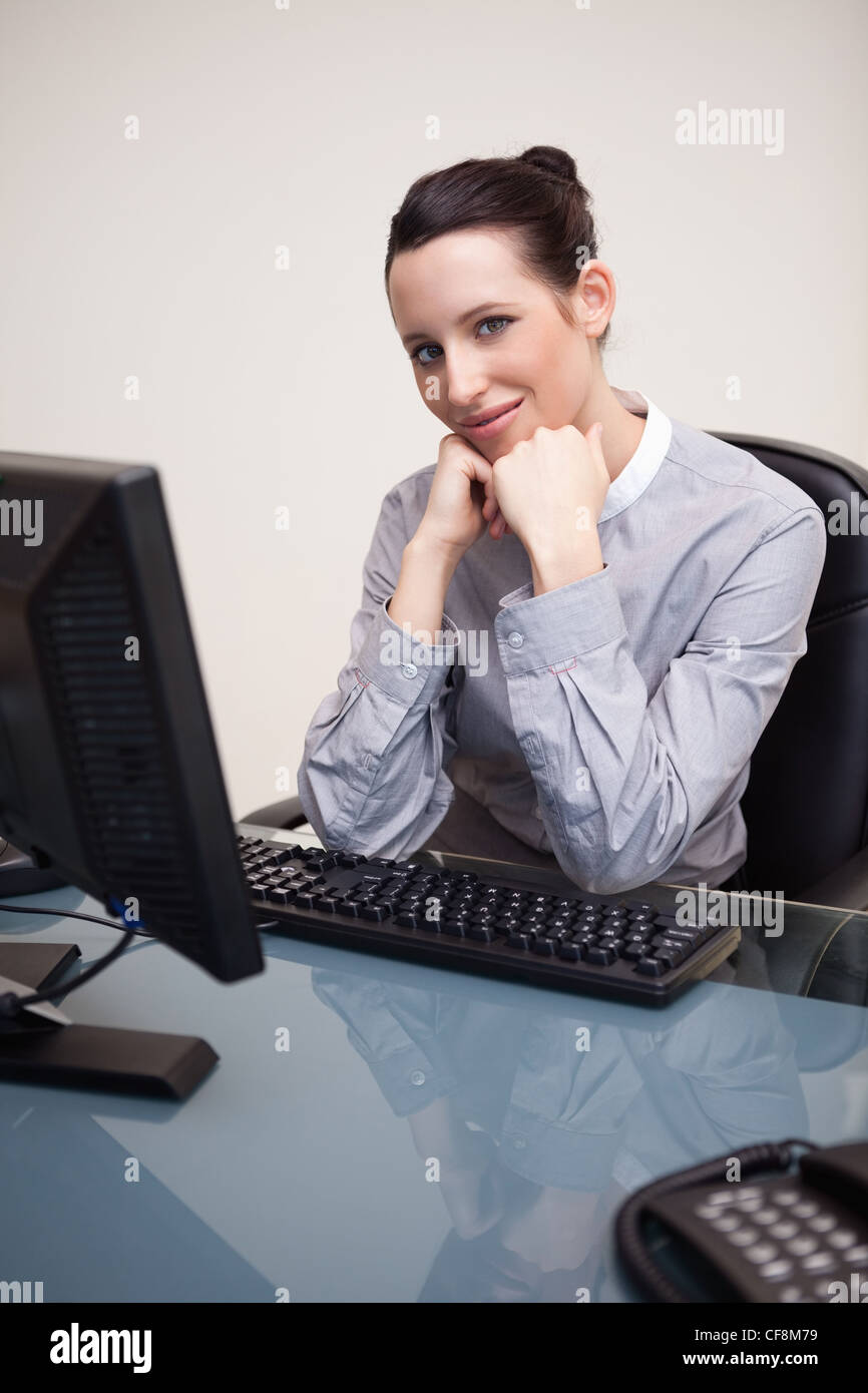 Smiling businesswoman waiting patiently at her computer - Stock Image