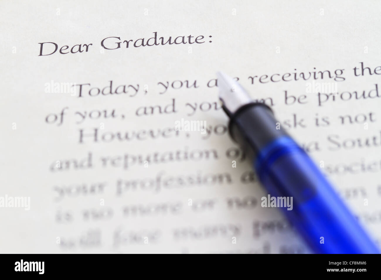 old fashioned fountain pen resting on diploma and graduation papers - Stock Image