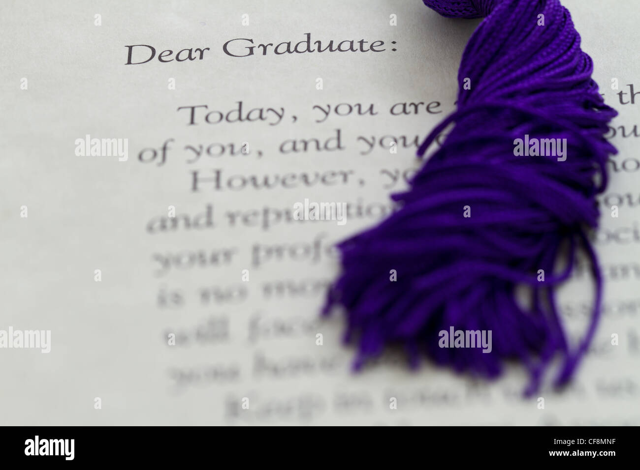 tassel/cord sitting on a graduation letter or diploma - Stock Image