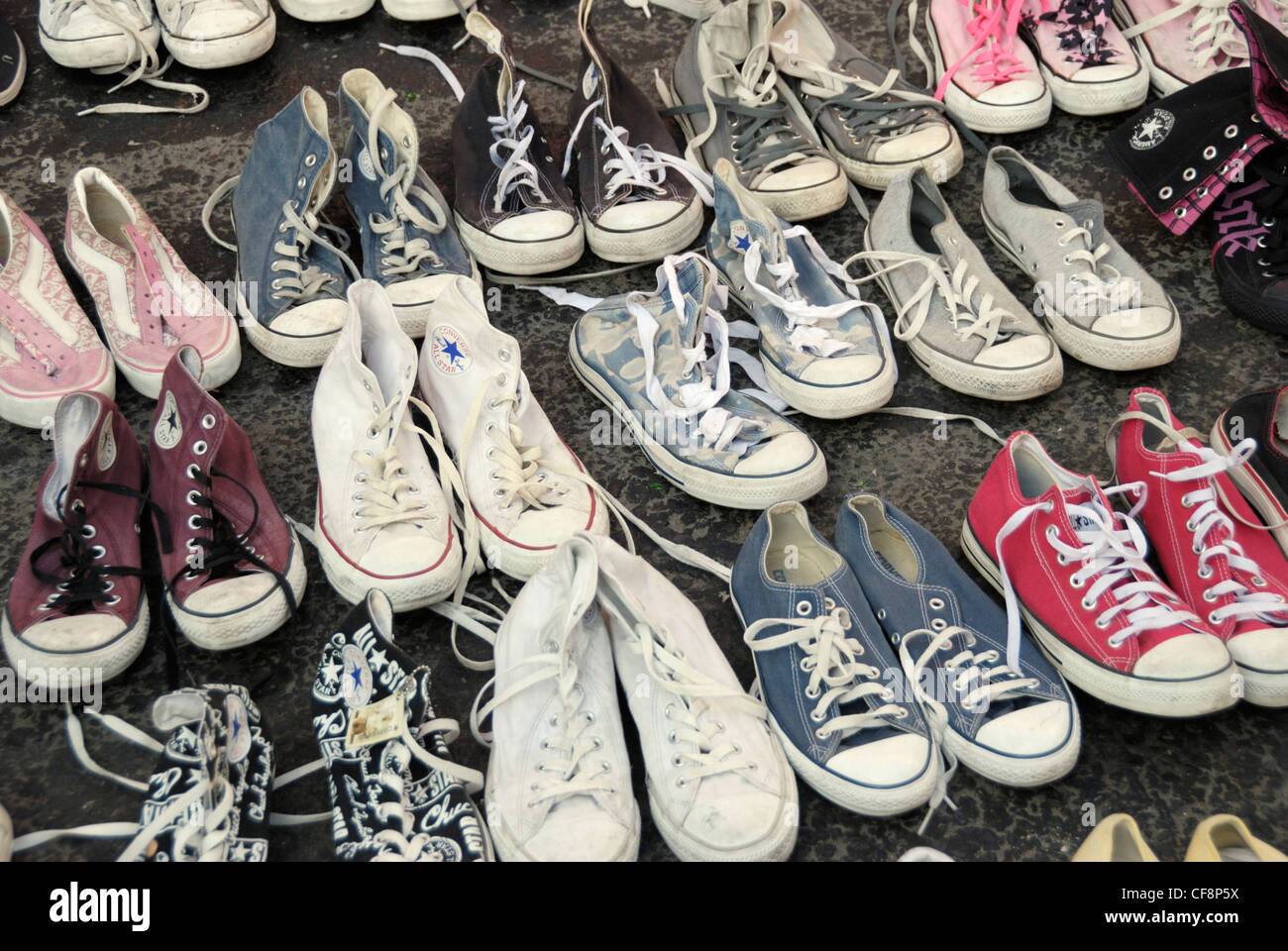 Second hand baseball shoes displayed on a pavement - Stock Image