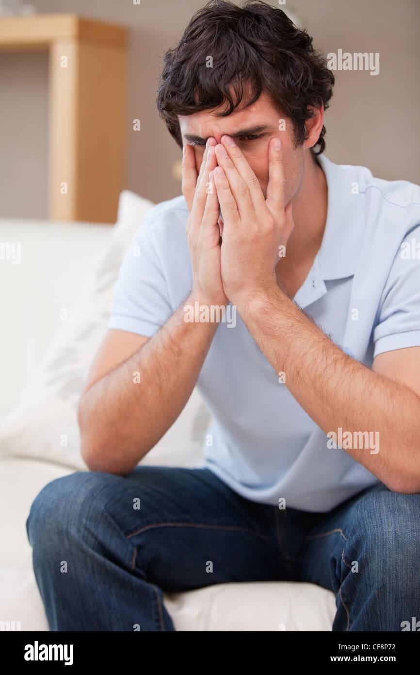 Desperate man sitting on the sofa - Stock Image
