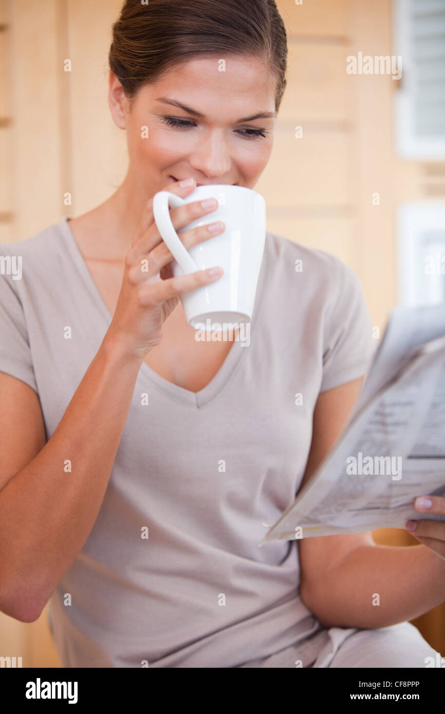 Woman taking a sip of coffee while reading newspaper - Stock Image