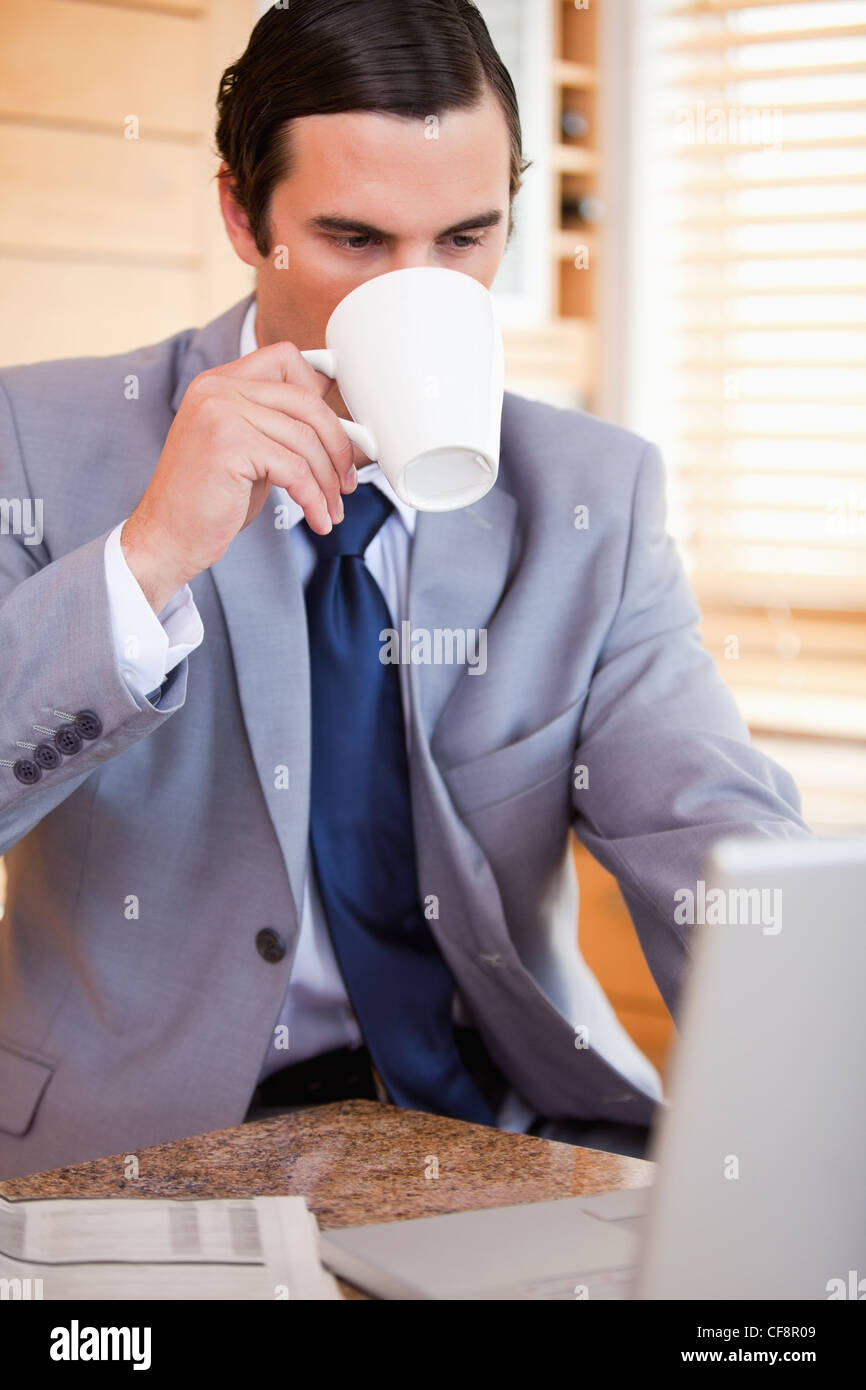 Businessman taking a sip of coffee next to his laptop - Stock Image