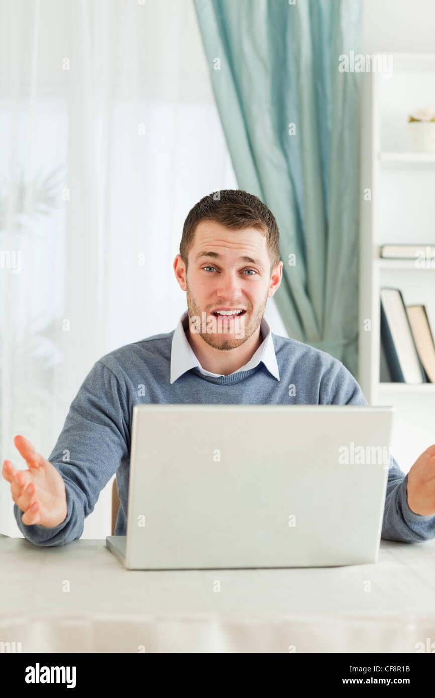 Businessman having no idea what's wrong with his laptop in his homeoffice - Stock Image