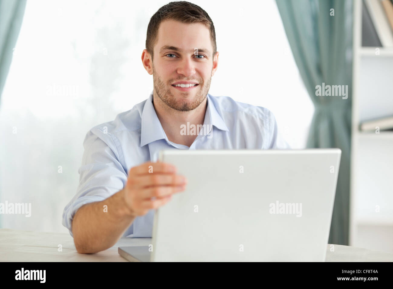 Smiling Businessman Sitting Behind A Table On His Laptop