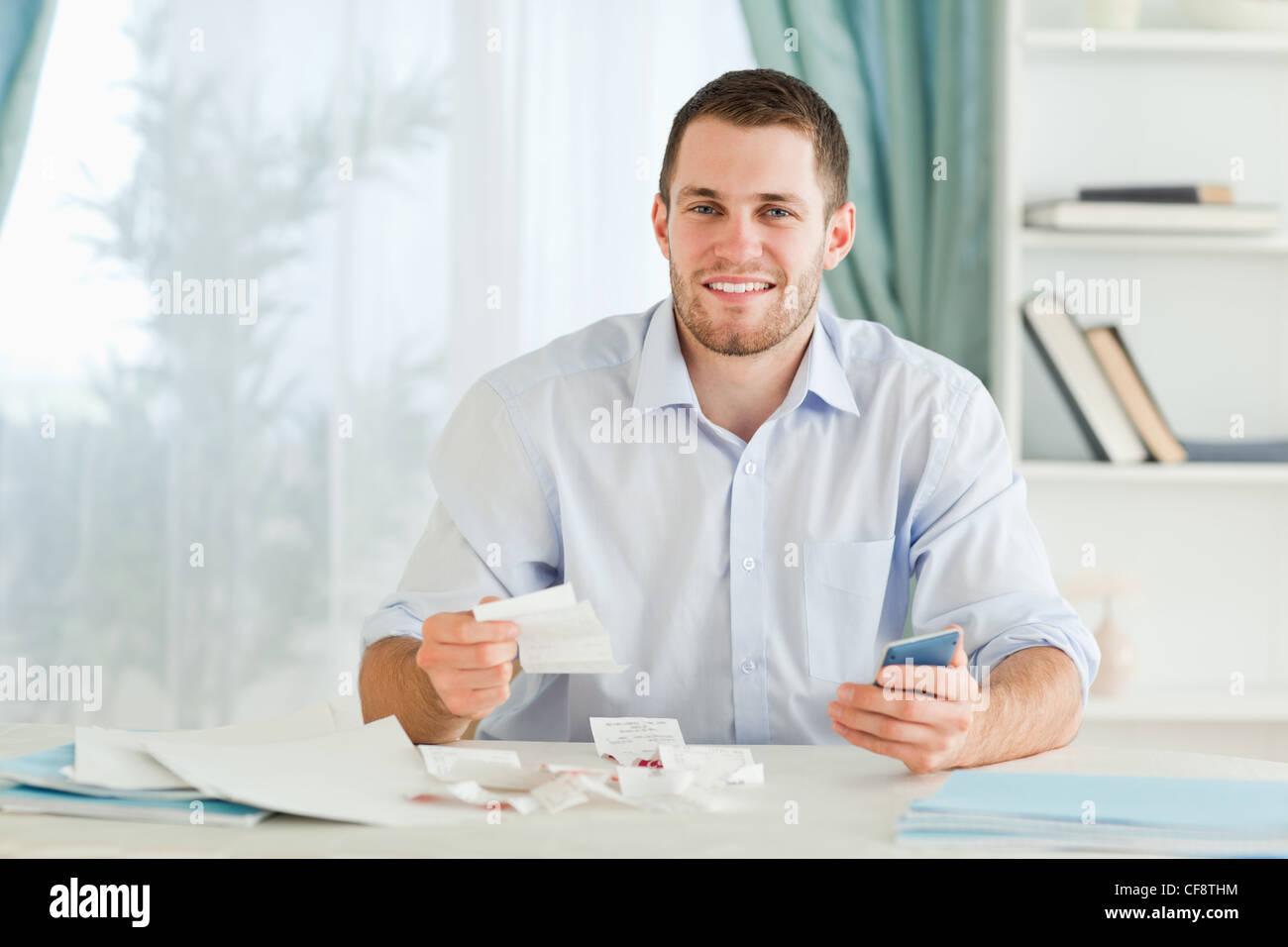 Businessman with pocket calculator checking bills Stock Photo