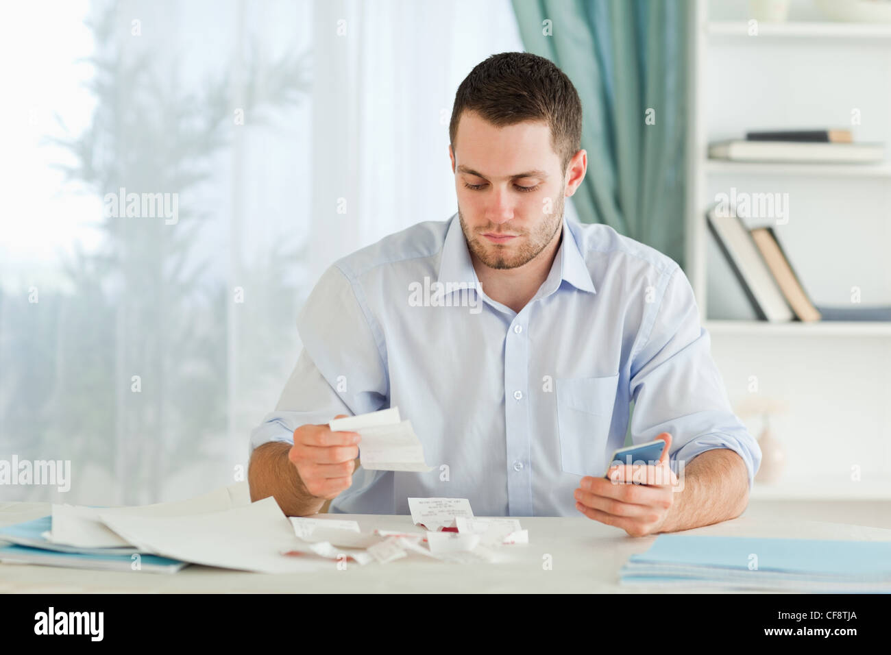 Businessman with pocket calculator checking invoices Stock Photo