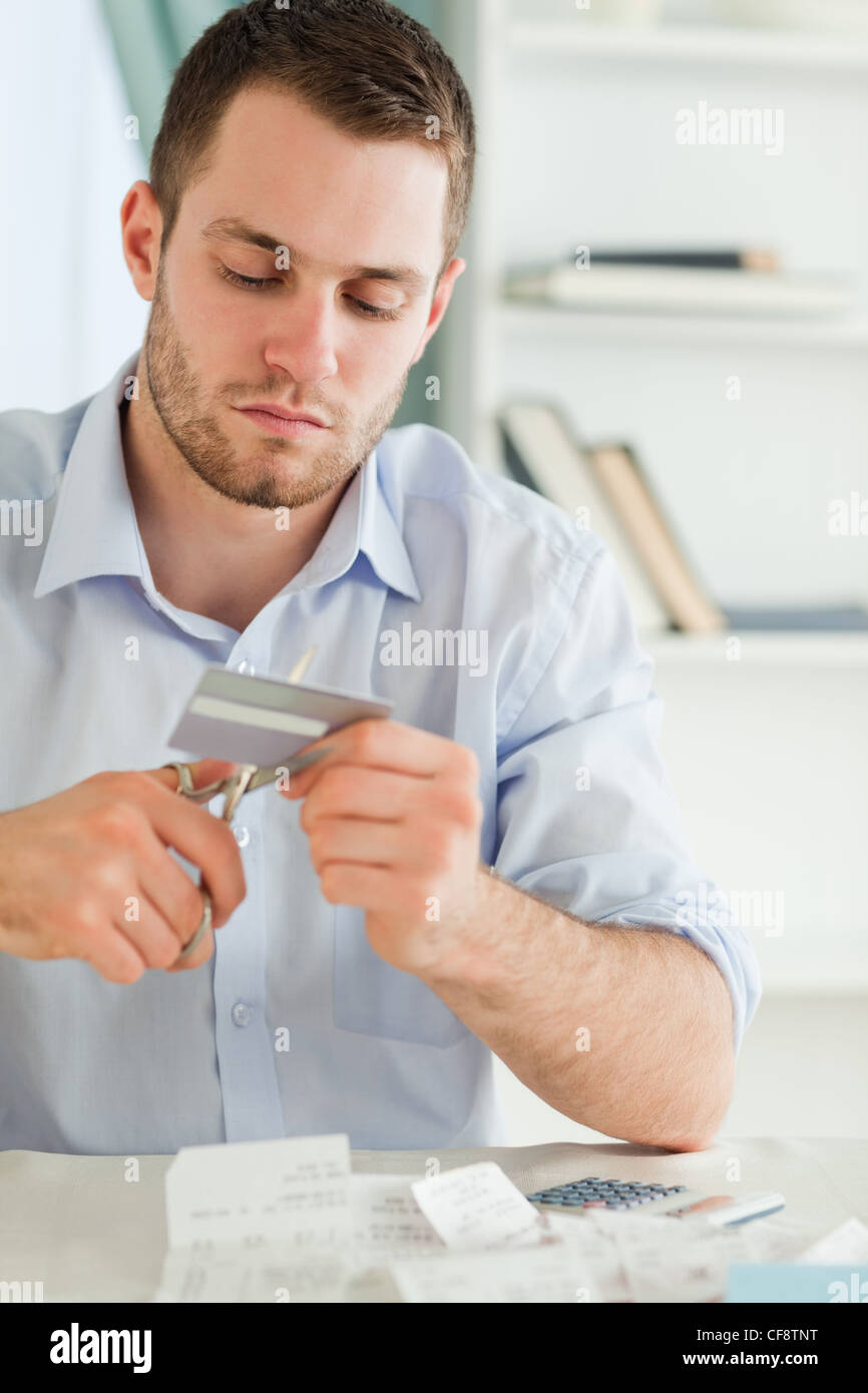 Businessman using scissor to destroy his credit card - Stock Image