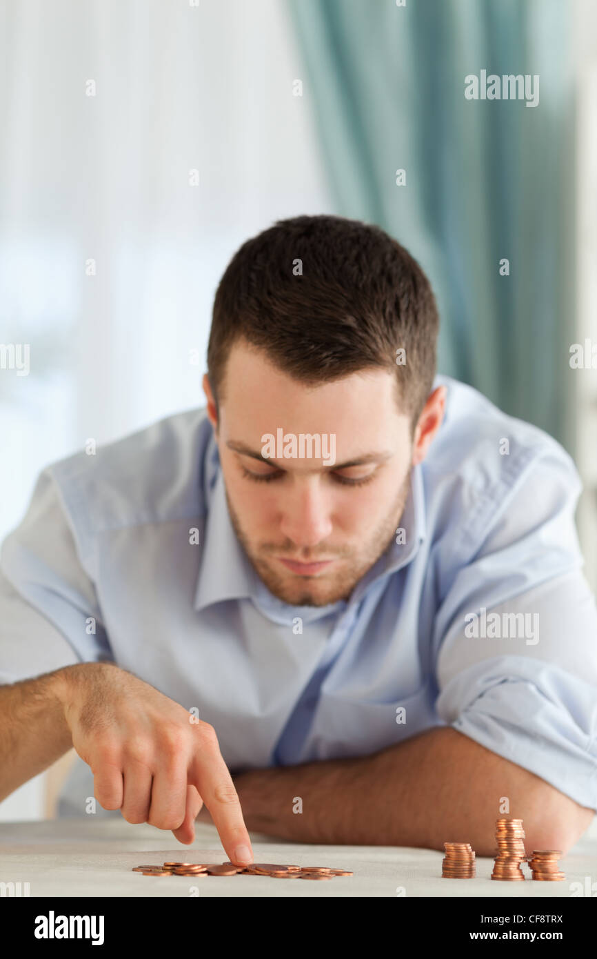 Desperate businessman counting change - Stock Image