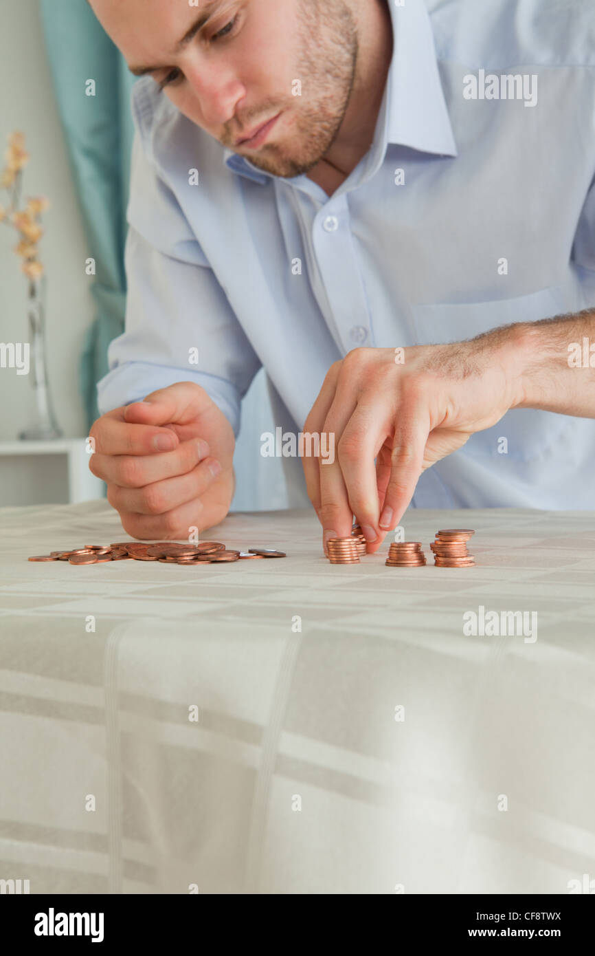 Desperate businessman counting his small change - Stock Image