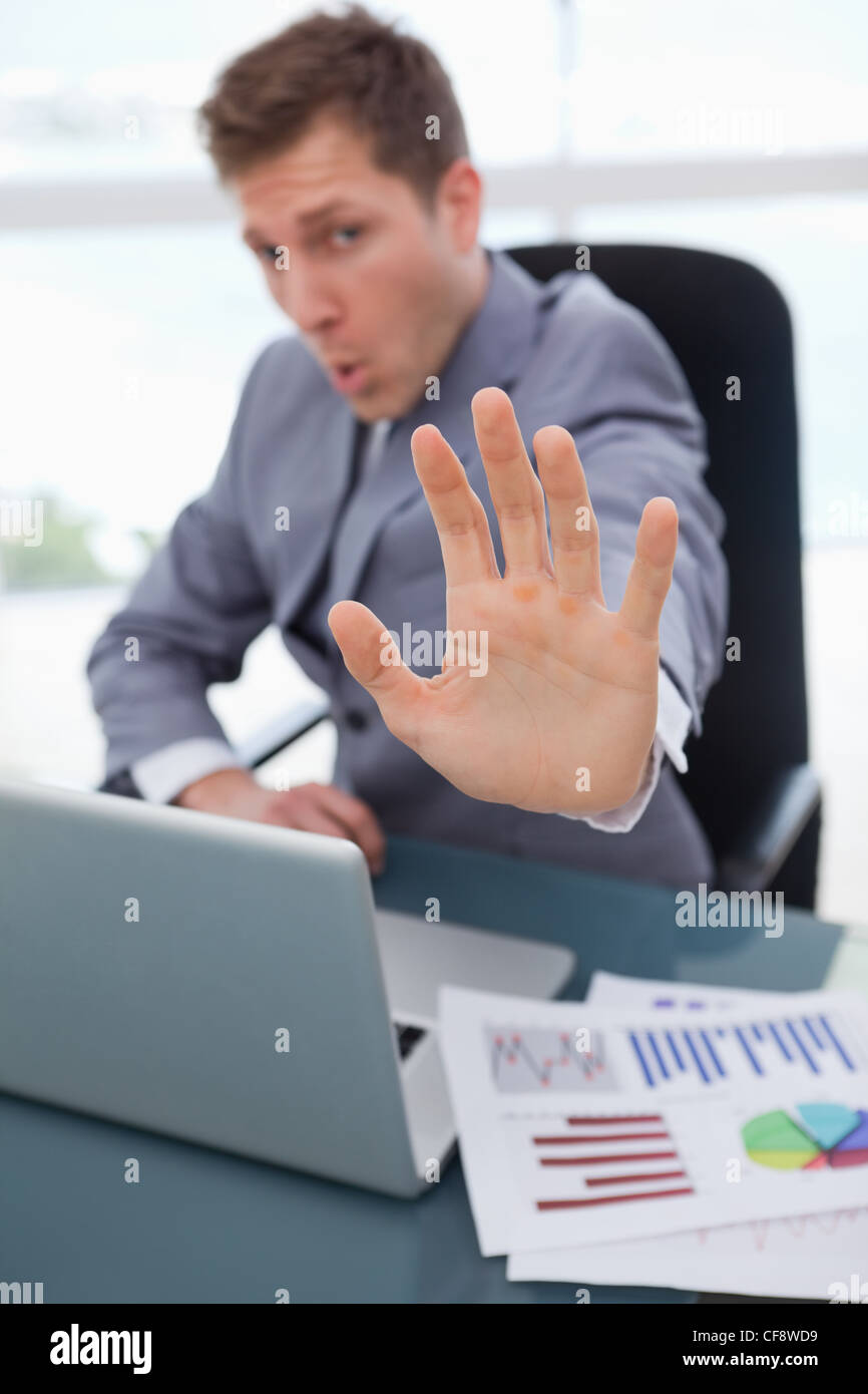 Hand of businessman used to signal stop - Stock Image