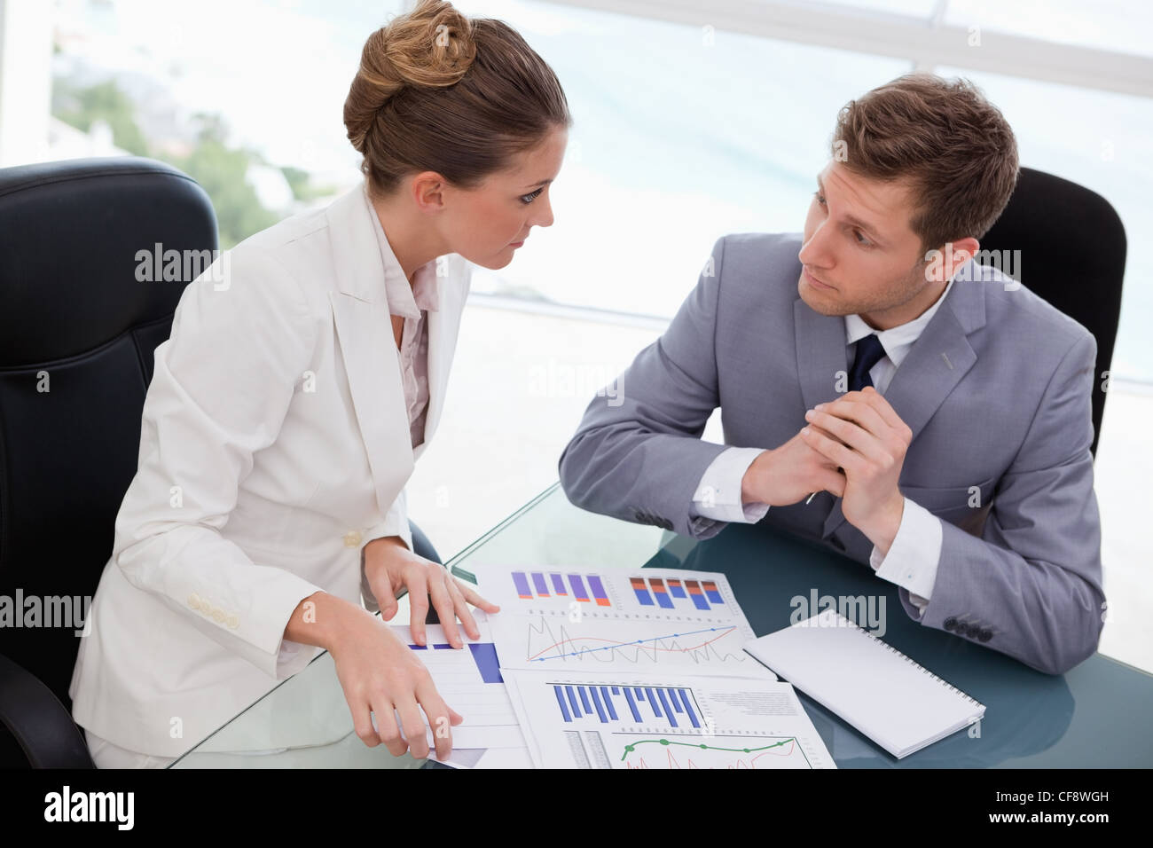 Business team deliberating on market research - Stock Image