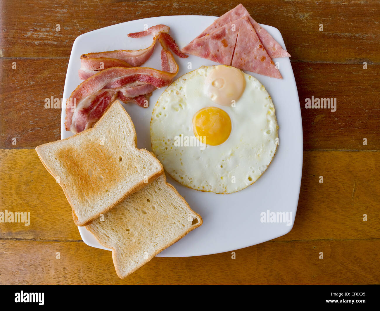 scrambled eggs with bacon and toast on white plate on the table - Stock Image