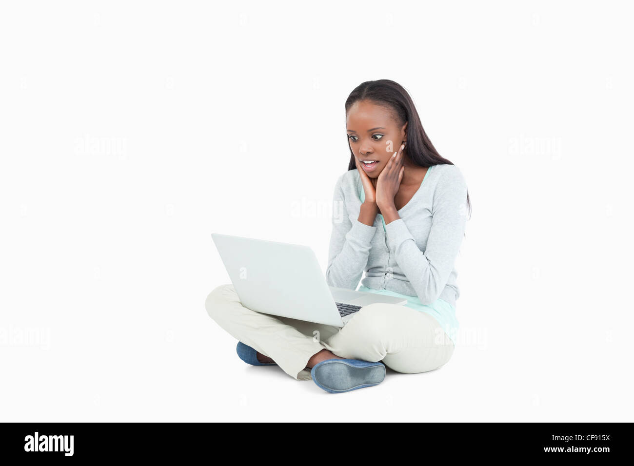 Young woman on the floor cannot believe whats on her screen - Stock Image