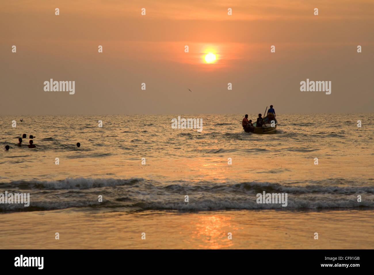 GOA, INDIA - 19 NOV 2011: indian boat and swimming children at sunset in the seaon Arambol beach in Goa Stock Photo