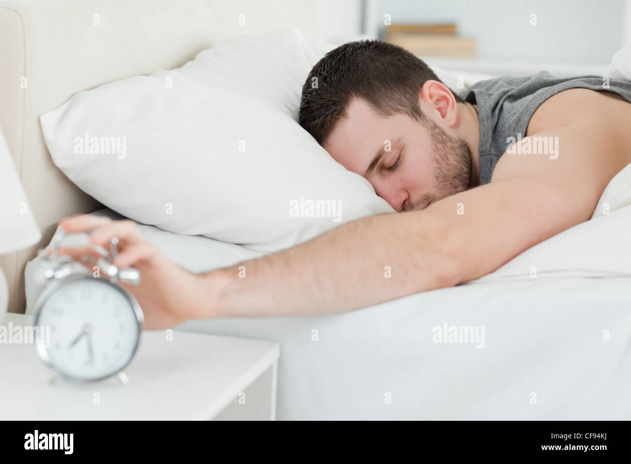 sleeping man being awakened by an alarm clock stock photo 43841830