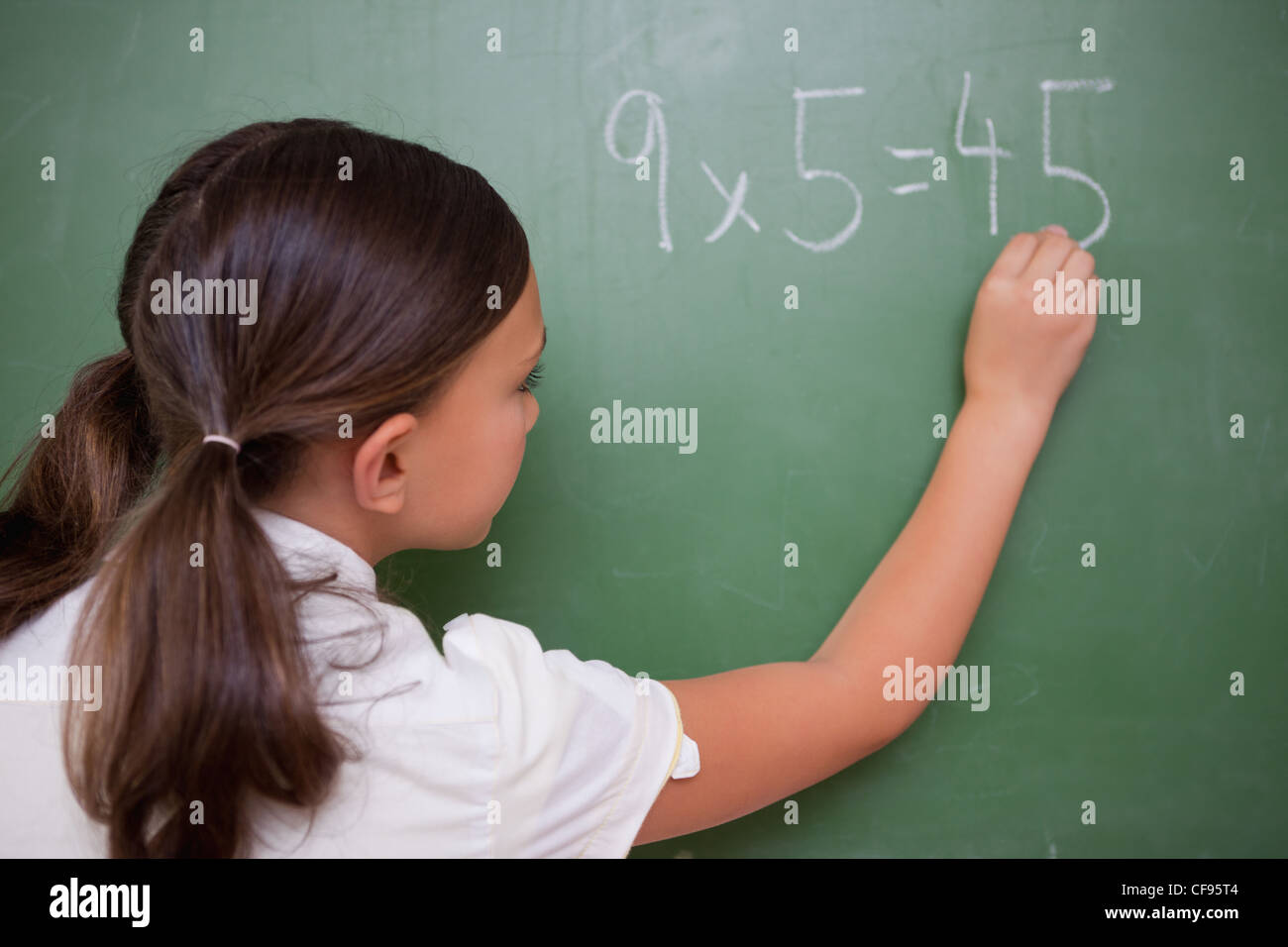 Schoolgirl writing a result - Stock Image
