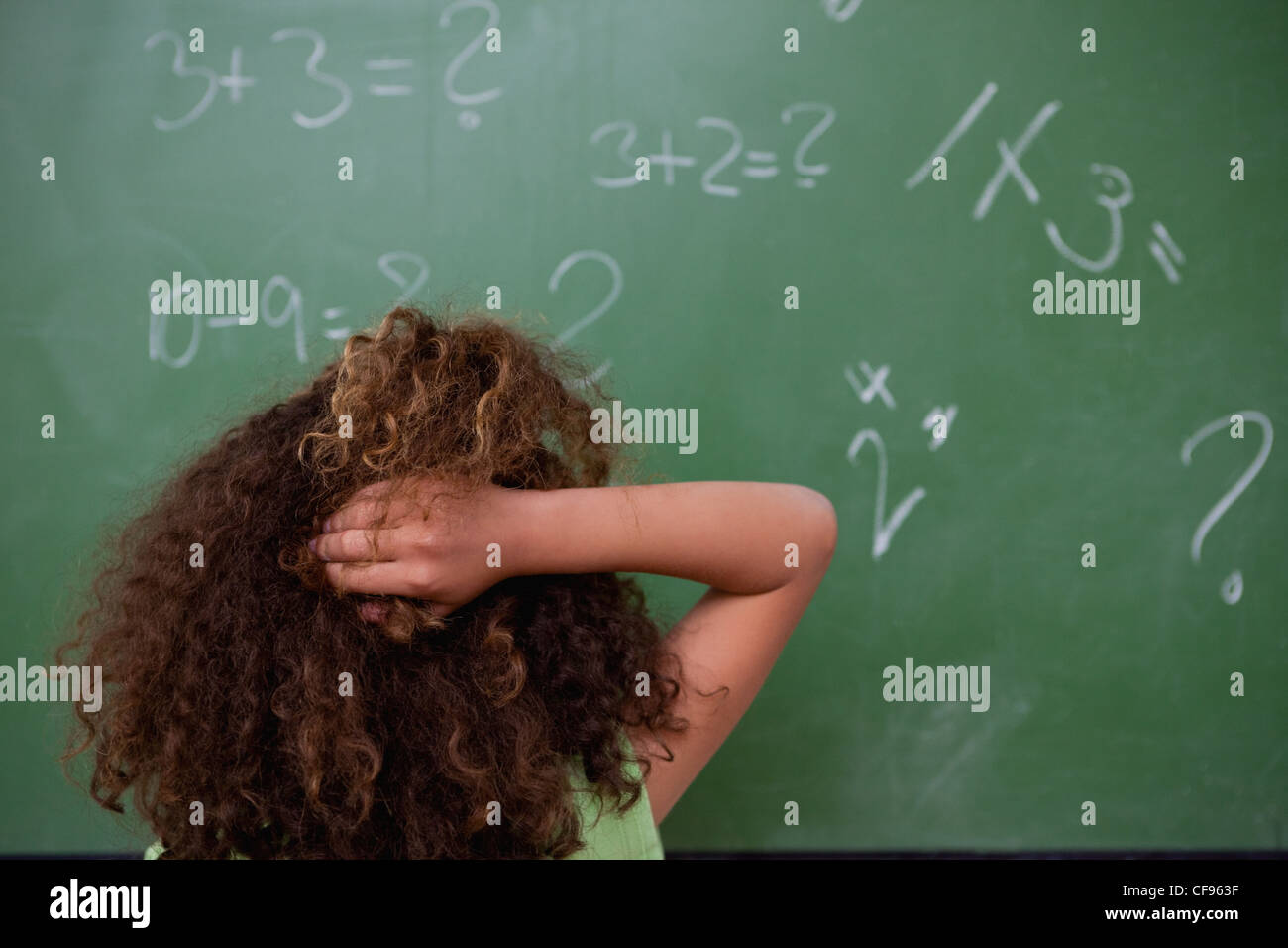 Schoolgirl thinking about mathematics while scratching the back of her head - Stock Image
