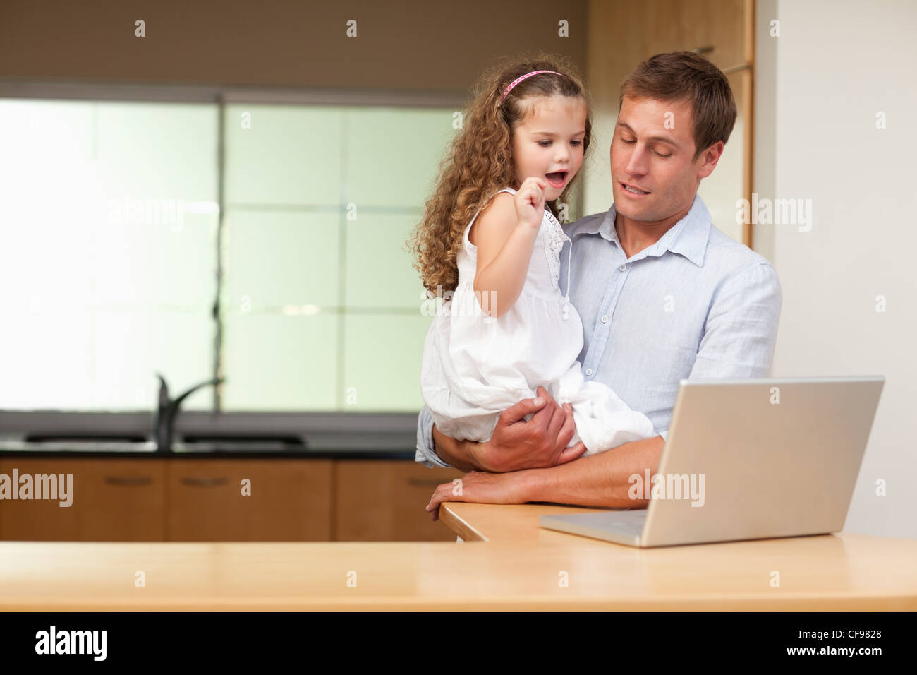 Girl is interested in her fathers laptop - Stock Image