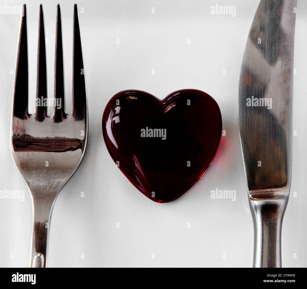 A heart placed between the fork and knife on a white background. The heart is a very blood like color. - Stock Image