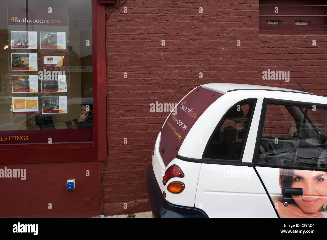 The fantasy of an estate agent's car and the reality of a desk-bound job seen through the office window. - Stock Image