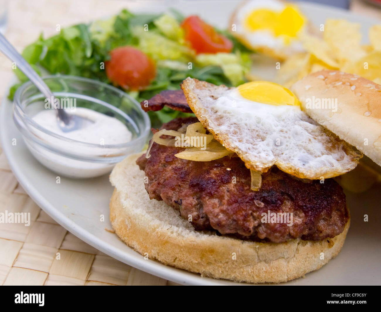 Grilled hamburger with fried egg and salad - Stock Image